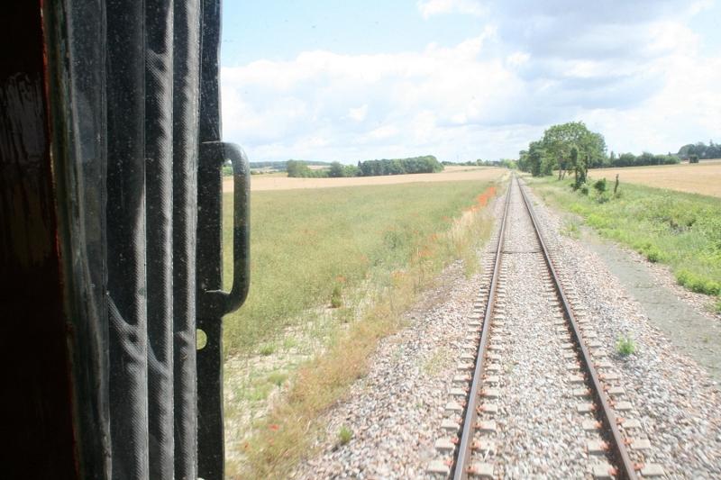 Vue depuis la queue du train, une section de ligne dans les champs de céréales (photo Ajecta-P.Berger)